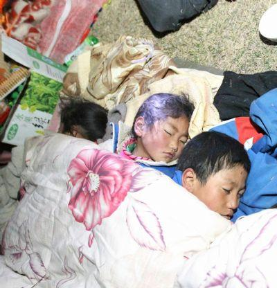 Children sleep in the open air as their parents build up a tent after a quake in Yushu County, northwest China's Qinghai Province, April 14, 2010. About 400 people have died and 10,000 others were injured after a 7.1-magnitude earthquake hit Yushu early on Wednesday. (Xinhua/Ding Lin)