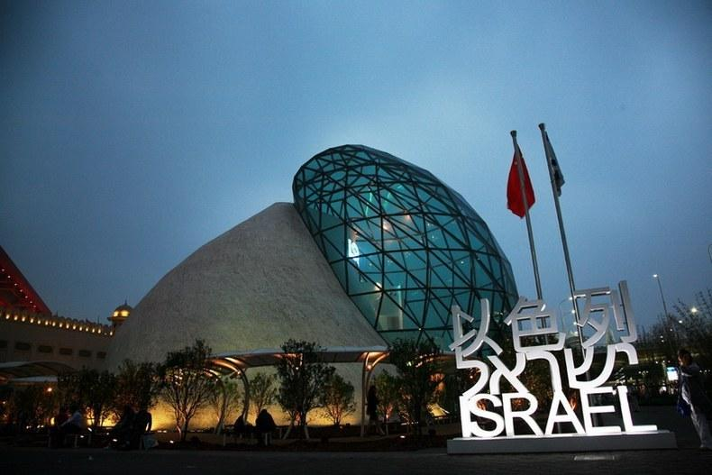"The Israel Pavilion is composed of two streamlined buildings hugging each other. The pavilion looks like two clasped hands, or a ""seashell�? One side of the ""seashell�?is made of authentic stone while the other is made from transparent glass. The design symbolizes Israeli innovation and technology as well as represents the dialogue between humanity and nature, the earth and the sky, as well as the past and the future."