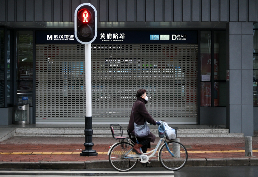 A resident rides by the closed Huangpulu Subway Station in Wuhan City on January 25, the 2020 Chinese Lunar New Year.
