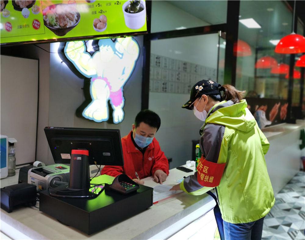 4月9日,天津市金融局下沉干部(右)在市内一家商场了解中小微企业复工情况,并送去防疫物资。新华社记者 刘惟真 摄