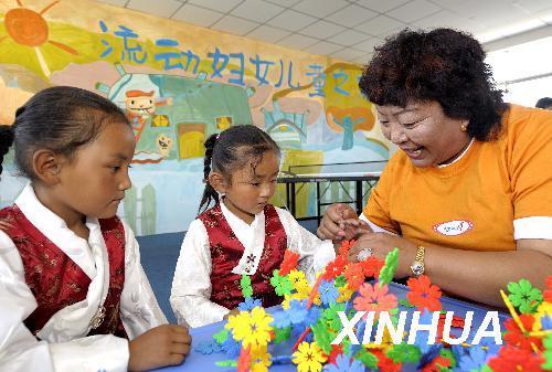 资料图片:6月25日,两名藏族儿童在流动妇女儿童之家学习插花.