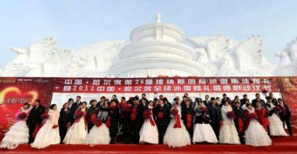Newlyweddedcouplesposeforphotosinfrontofasnowsculptureduringagroupweddingceremonyatthe26thHarbinInternationalIceandSnowFestivalinHarbin,HeilongjiangProvinceJanuary6,2010.Atotalof28couplesfromChinaandabroadparticipatedintheceremony.(Xinhua/LiYong)
