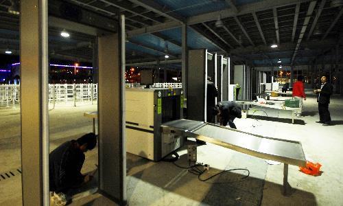WorkerssetupsecurityinspectionfacilitiesatthemainentrancetothePudongzoneoftheWorldExpoParkinShanghai,eastChina,March28,2010.TheExpoParkwillsoonstarttrialoperation.(XinhuaPhoto)