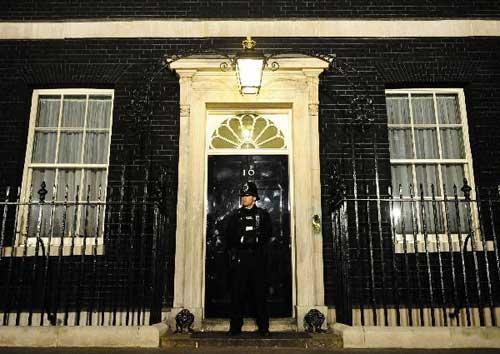 "AsecurityguardstandsinfrontofNo.10DowningStreetinLondon,Britain,intheearlymorningofMay7,2010.ThegeneralelectioninBritainresultedina""hungparliament""asnopartyisgoingtowinaclearmajority,preliminaryresultsshowedFriday.(Xinhua/ZengYi)"