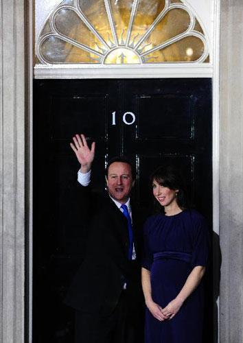 Britain's new Prime Minister Conservative party leader David Cameron (L) and his wife Samantha arrive at 10 Downing Street in London, on May 11, 2010. Cameron was appointed by Britain's Queen Elizabeth II as new prime minister. (Xinhua/Zeng Yi)