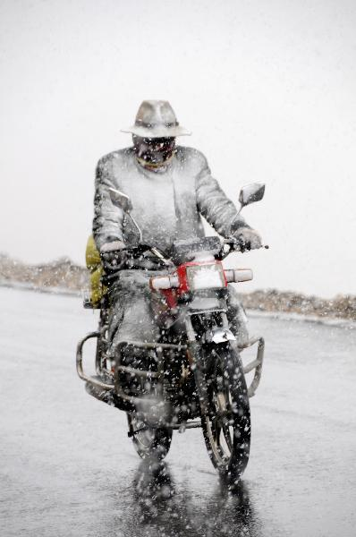 A man of Tibetan ethnic group drives his motorbike against the snow on the road in quake-hit Yushu Tibetan Autonomous Prefecture of northwest China's Qinghai Province, on May 13, 2010. (Xinhua/Wang Hongwei)