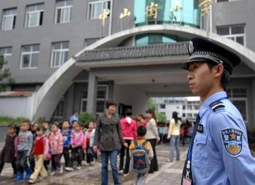 A policeman stands guard as pupils leave the school in Hanzhong City of northwest China's Shaanxi Province, May 14, 2010. A string of school attacks shocked China in recent weeks. Police have been ordered to beef up security at school compounds and nearby residential communities. (Xinhua/Ding Haitao)