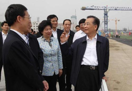 Chinese Premier Wen Jiabao (R) visits the construction site of integrated transportation complex of Tianjin West Railway Station in Tianjin, north China, May 14, 2010. (Xinhua/Liu Weibing)