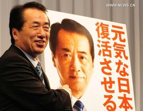 Japanese Prime Minister Naoto Kan, also president of Japan's ruling Democratic Party of Japan (DPJ), stands beside a campaign poster of the DPJ during a press conference in Tokyo, Japan, June 17, 2010. Japan's ruling Democratic Party of Japan on Thursday revealed its campaign pledges for July's upper house election.(Xinhua/Ji Chunpeng)