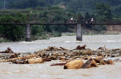 Shattered woods are brought by floods in the Beijiang River in Rongshui Miao Autonomous County, south China's Guangxi Zhuang Autonomous Region, June 18, 2010. Floods and landslides were triggered by rainstorm Friday in Rongshui, leaving 4 people dead and causing economic loss.(Xinhua/Zhang Yaohua)