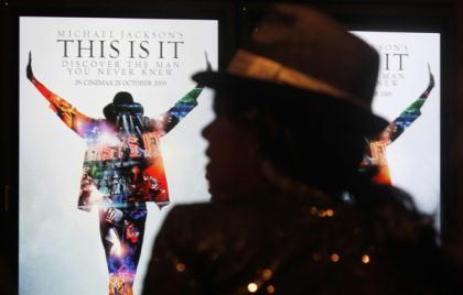"A Michael Jackson fan waits next to electronic posters at the Australian premiere of the documentary ""This Is It"", in Sydney October 28, 2009. The documentary includes interviews, rehearsals and backstage footage of Michael Jackson as he prepared for his shows in London. The film opens in Australia on October 29. (Xinhua/Reuters File Photo)"