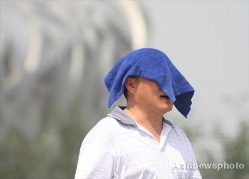 A man covers his head with a wet towel to shield himself from the sun in the Beijing Olympic Park on July 4, 2010.(Source: China Daily/Asianewsphoto)