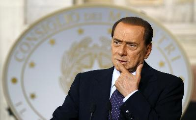 Italian Prime Minister Silvio Berlusconi looks on during a news conference with Malta's Prime Minister Lawrence Gonzi at Villa Madama in Rome July 8, 2010. Mr Berlusconi urges Italians to vacation in their own homeland in a new television advertisement aimed at boosting an economy struggling to emerge from recession.[Agencies]