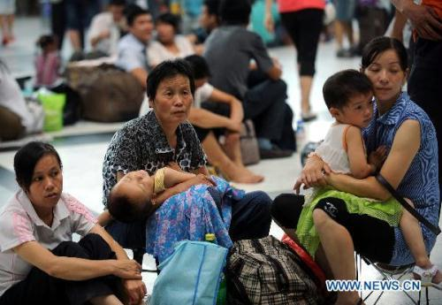 Passengers rest at Chongqing railway station in southwestern China's Chongqing Municipality, July 9, 2010. All train services were suspended due to thunderstorm on Friday morning in Chongqing Municipality, according to the local flood control authority.(Xinhua/Zhou Hengyi)