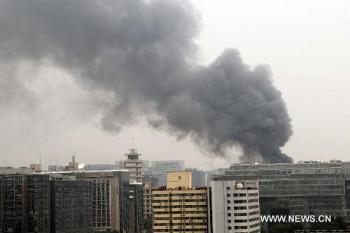 Smoke rises from a building that is on fire in the northeast corner of north Naoshikou street of Chang'an Avenue of Beijing, capital of China, July 9, 2010.(Xinhua/Gao Xueyu)