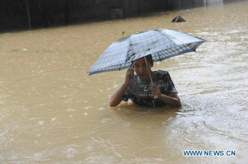 A citizen calls on a waterlogged road in Anqing, east China's Anhui Province, July 13, 2010. Heavy rainfall hit Anqing on Tuesday, causing severe flood in the city. Some 600 soldiers and more than 20 speed boats were dispatched to rescue people trapped by the flood. More than 20,000 residents have been transfered to safe places.(Xinhua/Xu Guokang)