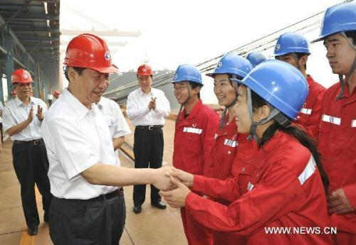 Chinese Vice President Xi Jinping (L, front), who is also a member of the Standing Committee of the Political Bureau of the Communist Party of China (CPC) Central Committee, shakes hands with an worker at an ore wharf in Caofeidian port, Tangshan City of north China's Hebei Province, July 18, 2010. Xi Jinping paid an inspection to Tangshan from July 17 to July 18.(Xinhua/Huang Jingwen)