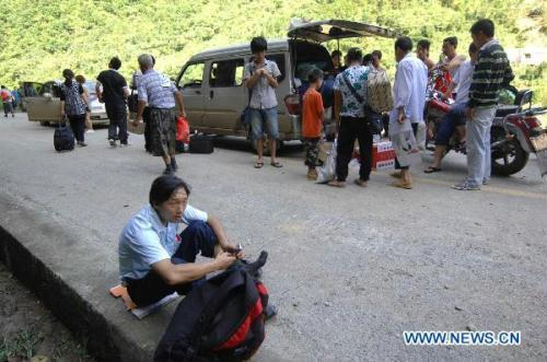 People wait on the street in Langao, southwest China's Shaanxi Province, July 19, 2010. Landslide blocked the road from Langao County to Muzhu Village on Monday. Transportations and communication were currently interrupted.(Xinhua/Ding Haitao)