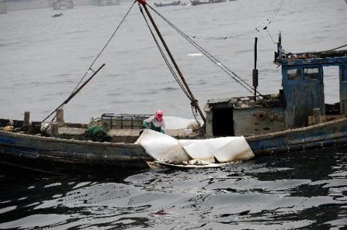 A worker cleans the oil on the sea in Dalian, a coastal city in northeast China's Liaoning Province on July 19, 2010. More than 500 fishing boats were set off Monday to clean up the crude oil that gushed into the sea after an oil pipe exploded at Dalian Xingang Harbor. Another 4 patrol boats kept monitoring the diffusion of oil and cleaning work, while laying out more protective boom. (Xinhua/Ren Yong)