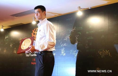 Chinese basketball star and Houston Rockets center Yao Ming displays his handprint prior to the charity gala for Yao Foundation CharityTour in Beijing, capital of China, July 23, 2010. (Xinhua/Meng Yongmin)