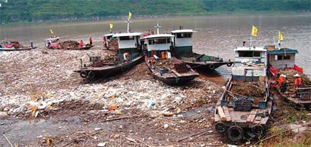 Workers on Monday scoop up trash floating on a section of the upper reaches of the Three Gorges Dam on the Yangtze River, ahead of the second flood peak anticipated in the region.(Photo: China Daily)