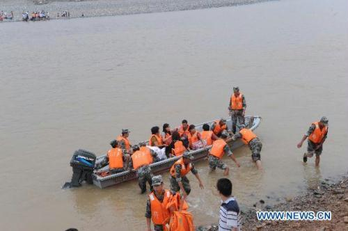 Armed policemen ferry local residents with a speed boat at the lower reaches of collapsed Yihe River Bridge in Luanchuan County, central China's Henan Province, July 27, 2010. The Yi River Bridge collapsed at about 5 p.m. Saturday in Luanchuan County, plunging 42 people on it into the rushing waters.  (Xinhua/Zhao Peng)
