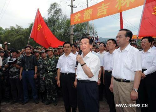 Chinese Premier Wen Jiabao (2nd R, front), who is also a member of the Standing Committee of the Political Bureau of the Communist Party of China Central Committee, addresses soldiers and local people in the flood-hit area in Yongji County of Jilin City, northeast China's Jilin Province on Aug. 3, 2010. Wen Jiabao visited Jilin Province to inspect the flood control operations on Tuesday and Wednesday. (Xinhua/Li Tao)