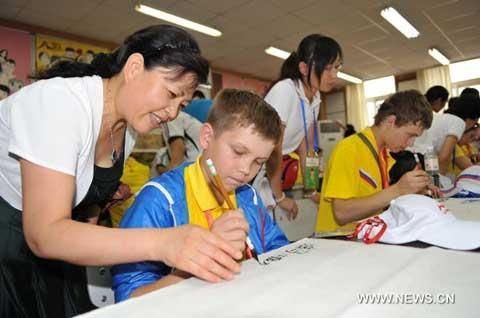 A Russian boy learns Chinese calligraphy during his summer camp tour in Qingdao, a coastal city in east China's Shandong Province, Aug. 5, 2010. A total of 200 Russian youngsters took part in the camp tour to experience Chinese culture. (Xinhua/Zhu Zheng)