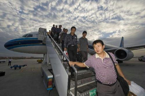 Chinese workers and engineers walk out of a chartered plane at the airport in Urumqi, capital of northwest China's Xinjiang Uygur Autonomous Region, Aug. 7, 2010. The first batch of 192 Chinese workers and engineers, who had once been trapped and rescued in flood-hit Pakistan's northwest province of Khyber Pakhtunkhwa, returned to China Saturday. (Xinhua/Zhao Ge)