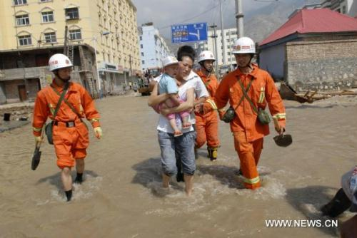 Firefighters evacuate residents to a safe place in landslides-hit Zhouqu County, Gannan Tibetan Autonomous Prefecture in northwest China's Gansu Province, Aug. 9, 2010. Recuers have saved 77 people from rain-triggered landslides in Zhouqu County as of 11 a.m. local time (0300 GMT) Aug. 9. (Xinhua/Hou Jun)