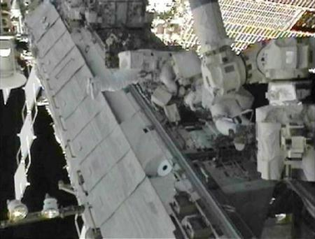 Spacewalkers Tracy Caldwell Dyson (L) and Doug Wheelock, attached to the International Space Station's robot arm, work to replace the failed ammonia coolant pump module on the station's S1 truss in this image from NASA TV August 11, 2010.(Xinhua/Reuters Photo)