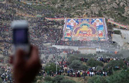 Drepung Monastery shows devotees the huge Thangka. Thousands of tourists flash their cameras to record the precious moment.