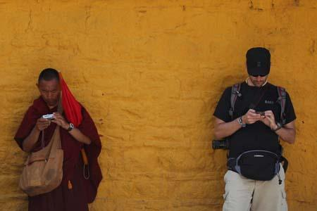 A lama and a foreign tourist share the same wall of Norbulingka to lean against and check electronic equipment. Zhang Tao / China Daily
