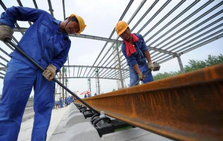 Workers lay rail tracks on the Beijing-Shanghai high-speed railway in Suzhou, east China's Anhui Province, Aug. 18, 2010. The 1,318-km high-speed railway connecting Beijing, China's capital in the north, and Shanghai, the country's economic center in the east, is to put in use in 2012, shortening the travelling time between Beijing and Shanghai to less than five hours, compared with the 10-hour journey by train between the two cities now. (Xinhua/Liu Junxi)
