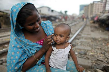 Hasina holds a mobile phone to her daughter Meem's ear, to talk to her grandfather, at a slum beside a railway line in Dhaka, Bangladesh, June 24, 2010.  (Xinhua/Reuters File Photo)