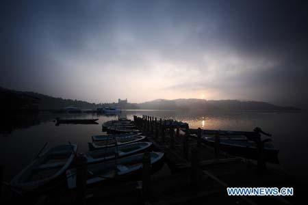 Boats are seen at a dock in Riyue Tan, or the Sun Moon Lake, southeast China's Taiwan, at dawn on Aug. 22, 2010. (Xinhua/Fei Maohua)