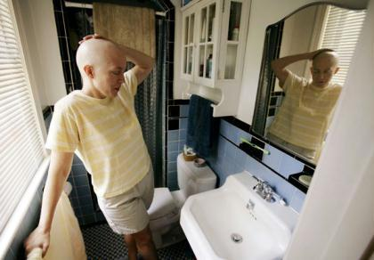 Cancer patient Deborah Charles stands in front of her bathroom mirror at her home in Washington May 25, 2007. (Xinhua/Reuters File Photo)