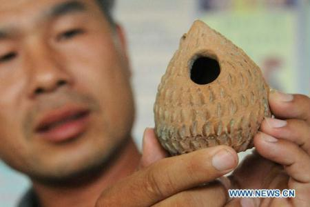 An archaeological worker shows an ancient pottery wind instrument at Xiaoli Village in Baixiang County, north China's Hebei Province, Aug. 30, 2010. Since June, archaeologists have unearthed abundant cultural relics at the village's Yangshao site, dating back to 5,700 to 6,300 years ago. (Xinhua/Gong Zhihong)