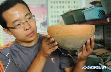 An archaeological worker shows an ancient earthen bowl at Xiaoli Village in Baixiang County, north China's Hebei Province, Aug. 30, 2010. (Xinhua/Gong Zhihong)