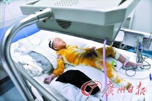 2岁的小婷婷全身被包裹着躺在病床上。记者何波摄