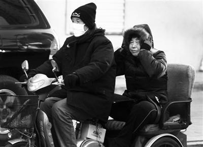 昨日,北京大风中行人将自己包裹得严严实实