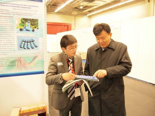 中国驻德国大使馆公使衔参赞孟曙光先生(右一)在九生堂展位前询问了解酶法多肽专利产品三九蛋白肽有关情况