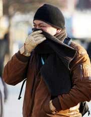 """近日北京大风降温,今天早上更是寒风凛凛。这对参与报道""""两会""""提前抵达会场的记者们真是一个严峻的考验。图为迎着寒风到达人民大会堂的记者们。"""