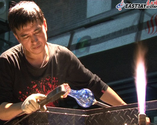 已有30多年玻璃制作经验的周师傅在为记者吹制的玻璃花瓶做最后打磨。