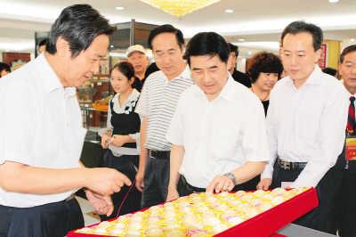 中国民间文艺家协会党组书记罗杨(右二)在观看表现56个民族题材的蛋雕作品。高杨 摄