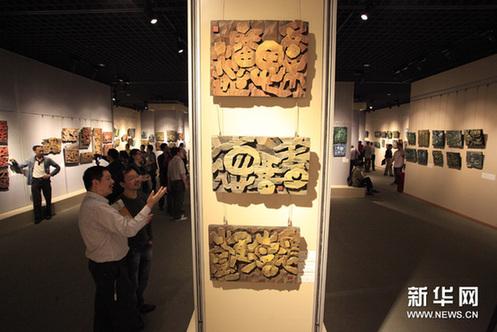 9月23日,参观者在艺术展上欣赏刻字艺术作品。新华网图片 许小峰 摄