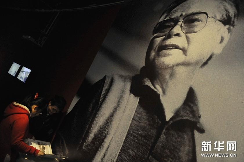 11月18日,两名观众在中国美术馆内展出的一张关山月的巨幅照片前欣赏关山月的画册。