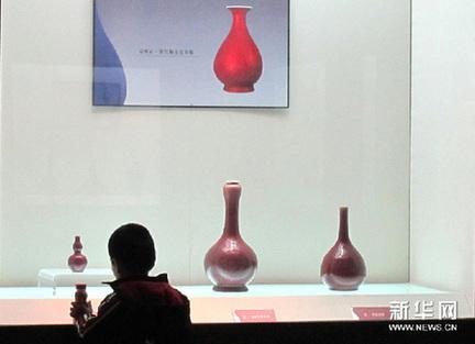 """11月20日,一个小朋友在""""馆藏单色釉瓷器展""""上观看单色釉瓷器精品。新华网图片 徐速绘 摄"""