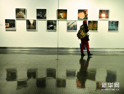 11月25日,参观者在欣赏系列摄影作品《穿越》。新华网图片 龙巍 摄