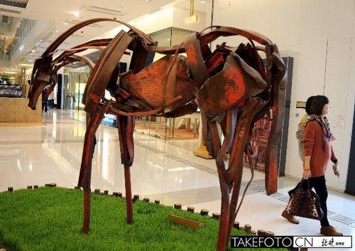 12月1日,两位顾客从香港K11摆设的一件雕塑作品《跃马》旁走过。